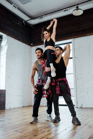 strong multicultural men holding attractive woman while posing in dance studio Stock Photo