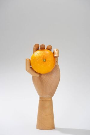 Wooden hand of doll with fresh mandarin on grey background