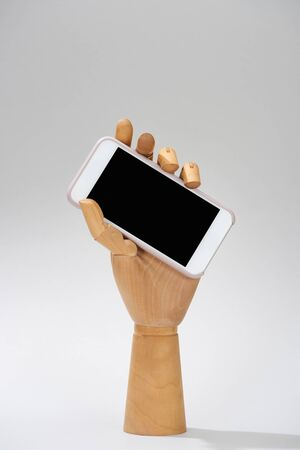 Wooden hand of doll with smartphone with blank screen on grey background Stock Photo