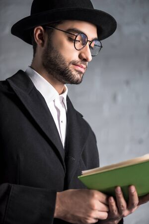 handsome and young jewish man in glasses reading book Reklamní fotografie