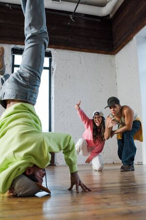 selective focus of emotional dancers looking at african american man breakdancing in dance studio Stock Photo