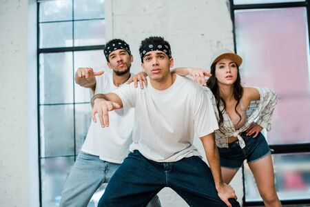 stylish multicultural dancers posing while dancing hip-hop in dance studio Banque d'images