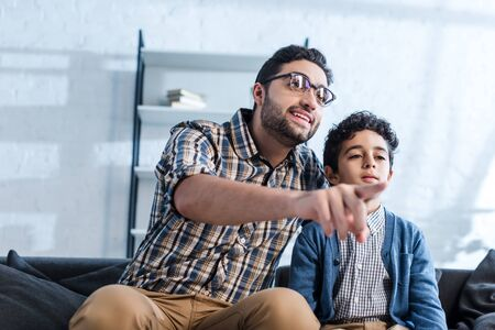 smiling jewish father pointing with finger and watching tv with son