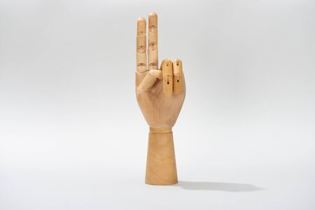 Wooden hand of doll with peace sign on grey background Stock Photo