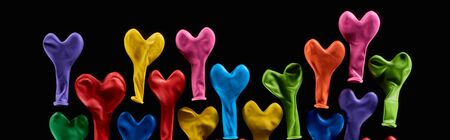 Top view of colorful rubber balloons in heart shape isolated on black, panoramic shot