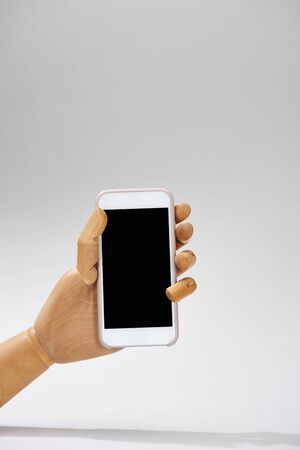 Hand of wooden doll with smartphone on grey background Stock Photo