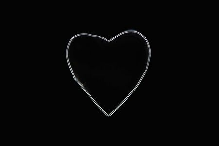 Top view of metal wire in heart shape isolated on black