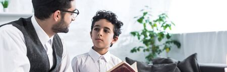 panoramic shot of jewish father and son talking and holding tanakh in apartment Banque d'images