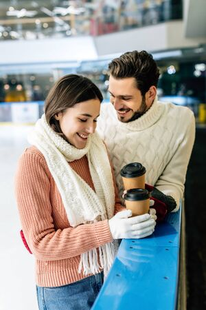 beautiful positive couple holding coffee to go on skating rink