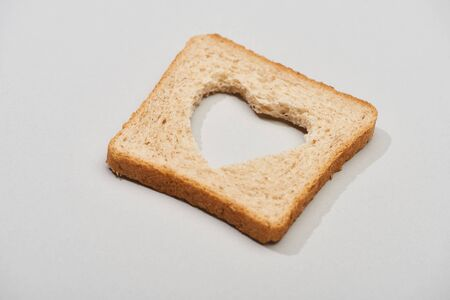 Bread slice with carved heart shape on grey background