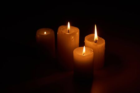 brandende kaarsen gloeien in het donker op zwarte achtergrond Stockfoto