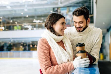 smiling couple holding coffee to go on skating rink Stockfoto