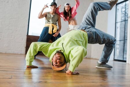 selective focus of african american man breakdancing near emotional dancers