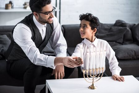 smiling jewish father and son holding candle in apartment