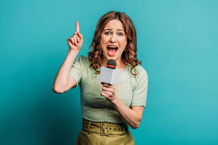 angry journalist pointing up with finger while shouting in microphone on blue background Stok Fotoğraf