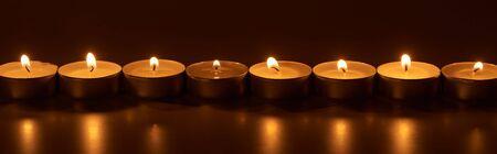 burning white candles glowing in dark, panoramic shot