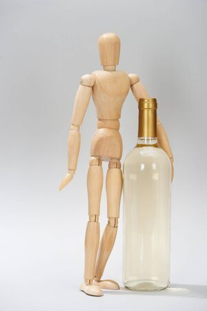 Wooden puppet beside bottle of white wine on grey background