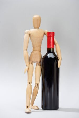 Wooden doll and bottle of red wine on grey background