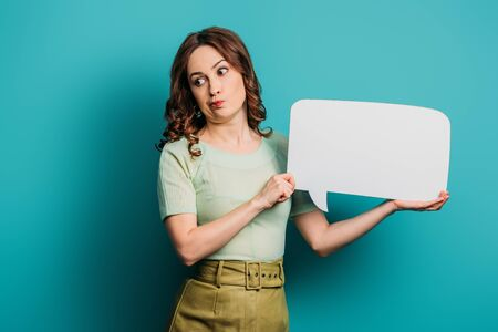 skeptical girl grimacing while holding speech bubble on blue background Stok Fotoğraf - 137726964
