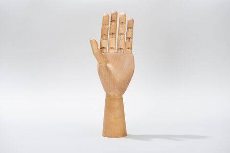 Hand of wooden doll on gray background