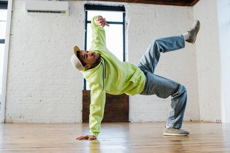 stylish african american man breakdancing in dance studio