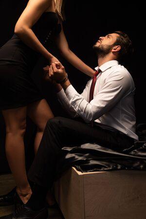 Apasionada pareja de amantes jugando con esposas en la cama en una habitación oscura
