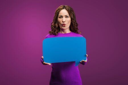 surprised woman holding speech bubble on purple background