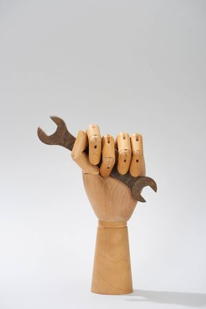 Wooden hand of doll with adjustable wrench on grey background