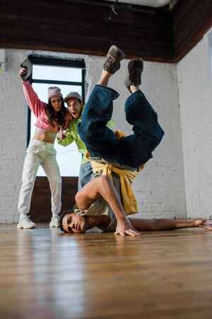 selective focus of handsome man breakdancing near excited multicultural dancers