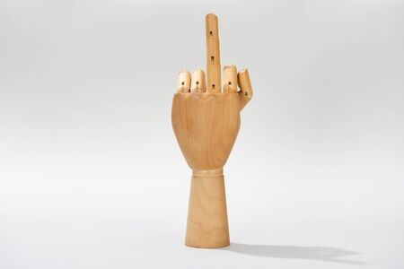 Wooden hand with middle finger gesture on grey background