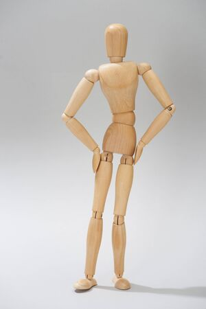 Wooden dummy with hands on hips on grey background