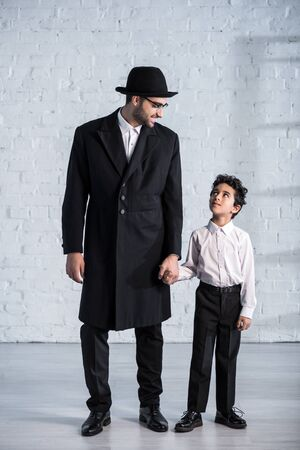 smiling jewish father and cute son holding hands and looking at each other