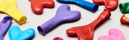 Panoramic shot of colorful heart shaped balloons on grey background
