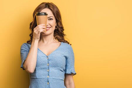 smiling girl covering eyes with paper cup on yellow background Stock Photo