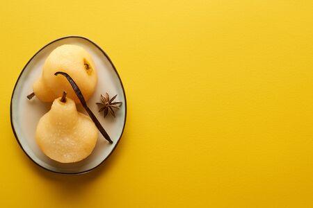 vue de dessus d'une délicieuse poire au vin à l'anis sur plaque sur fond jaune