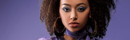 panoramic shot of attractive african american woman with earrings looking at camera isolated on purple