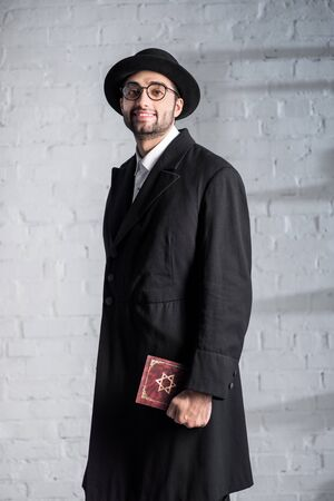 handsome and smiling jewish man in glasses holding tanakh