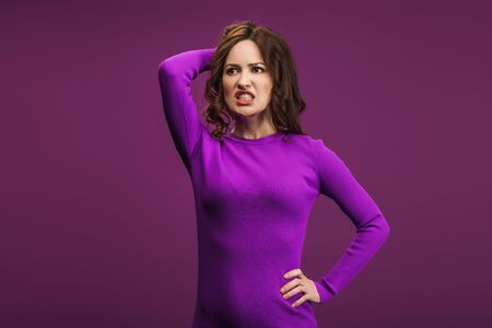 angry woman standing with hand on hip and touching head on purple background Stok Fotoğraf - 137727738