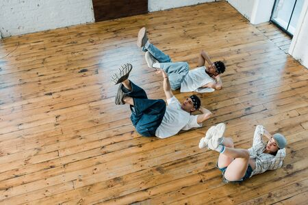 overhead view of trendy girl lying on floor with multicultural dancers while breakdancing in dance studio