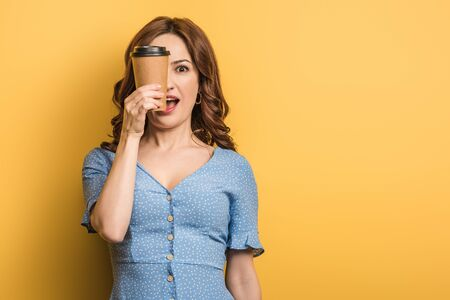 cheerful woman covering eye with paper cup on yellow background