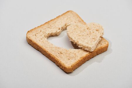 Slice of bread with carved heart shape on grey background