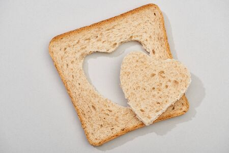 Top view of slice of bread with carved heart on grey background