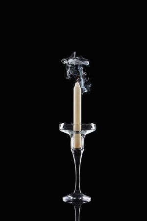 extinct white candle in glass candlestick with smoke on black background