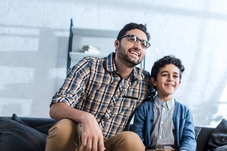 smiling jewish father and son watching tv in apartment