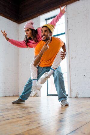 happy african american man piggybacking attractive dancer