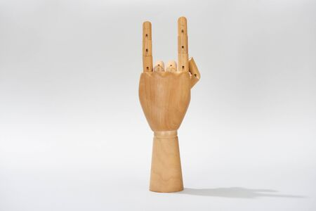 Wooden hand of doll with rock symbol on grey background