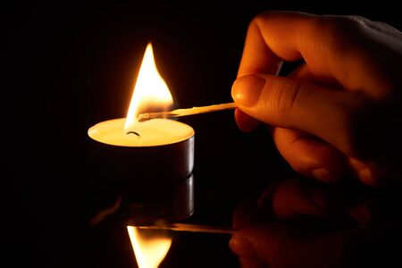 selective focus of woman lighting up candle with match isolated on black