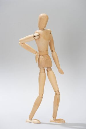 Wooden doll with hand on hip on grey background Stock Photo