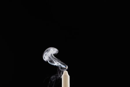 extinct white candle with smoke on black background