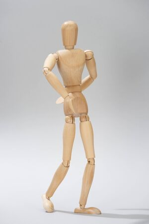 Wooden puppet with hinges on grey background Stock Photo